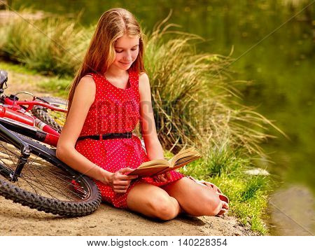 Girl wearing red dress read book on beach of river. Girl arrived on bicycle. Girl leaning and rest near bicycle on river beach in park outdoor. Tall grass on river bank