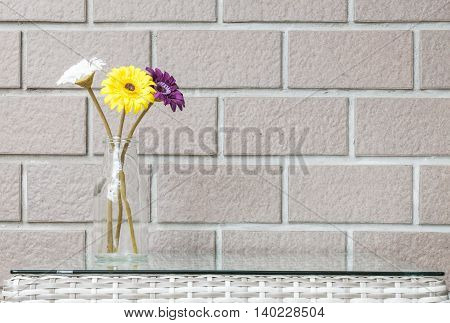 Closeup artificial colorful flower on transparent glass bottle on wood weave table on blurred brown brick wall texture background beautiful interior in relaxation concept of house