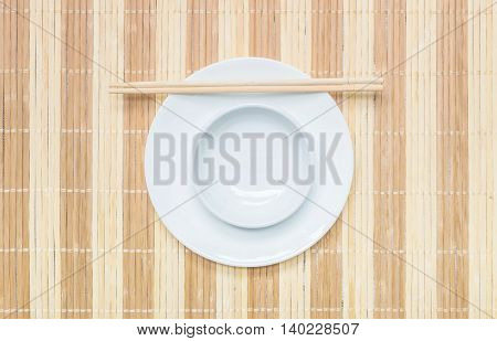 Closeup white ceramic chalice on circle dish wood chopsticks on wood mat textured background on dining table in top view
