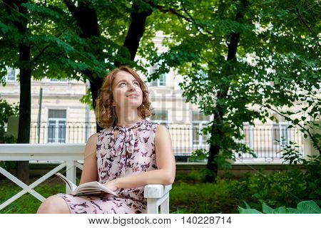 Beautiful dreamy girl resting in green park with book on warm summer day
