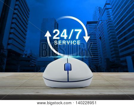 Wireless computer mouse with button 24 hours service icon on wooden table over city tower background Full time service concept