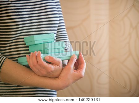Woman holds small blue gift boxes. Present.