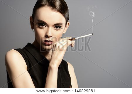 Fashion shot of an elegant brunette model smoking. Makeup and hair in the sixties style. Studio shot.