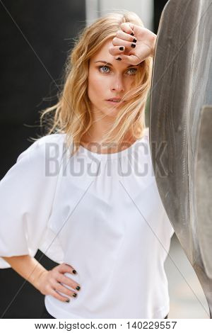 Portrait of worried pensive young blonde business woman outdoors