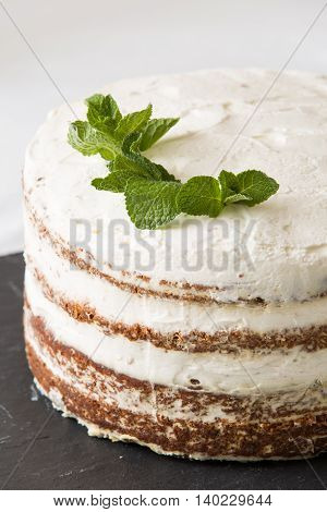 Close-up of delicious white cream icing cake with mint leaves served on the black board. Homemade naked cake with cream decorated with mint. Birthday pie.