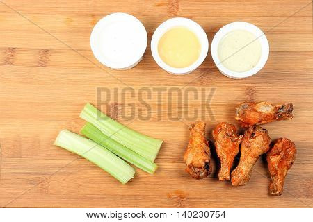Chicken buffalo wing salary stick dip sauce on wooden board