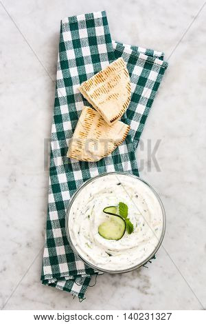 Tzatziki sauce in bowl and pita bread on marble