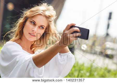 Young beautiful blonde woman with natural makeup in white blouse doing self portraits sitting on park bench