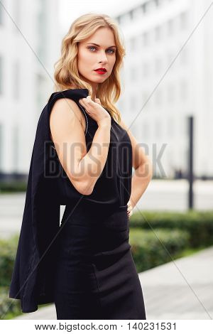 Portrait of intelligent blonde woman on business center background. Concept of successful modern business life. Split toned photo