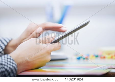 Hands of businessperson using digital tablet at office