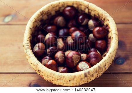 nature, season, autumn and botany concept - close up of chestnuts in wicker basket on wooden table