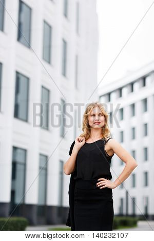 Portrait of gorgeous blonde woman on white modern office building background