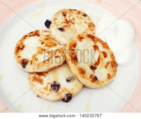 freshly baked cottage cheese pancakes with raisin and sour cream on white and pink plate