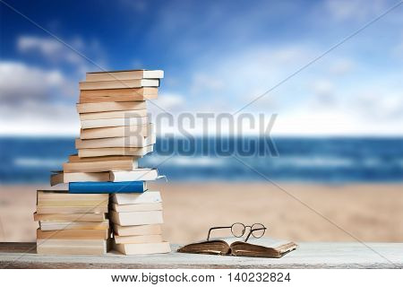 Stack Of Travel Guides Before A Empty Beach