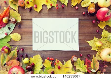 nature, season, advertisement and decor concept - close up of white paper sheet in frame of autumn leaves, fruits and berries on wooden table
