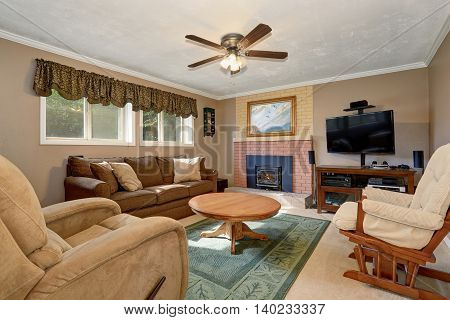 Typical American Living Room With Brown Couch And Fireplace.