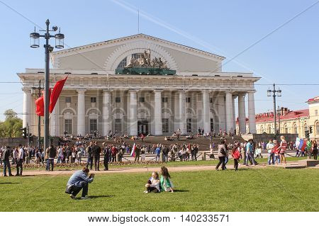 St. Petersburg, Russia - 9 May, Exchange Building on Vasilyevsky Island, 9 May, 2016. Vacationers people on the lawns and gardens in the city.
