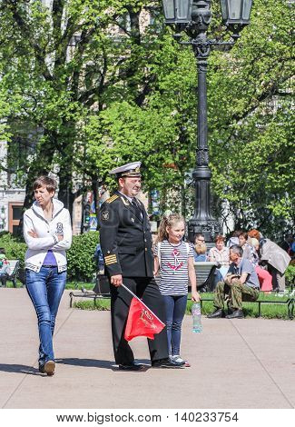 St. Petersburg, Russia - 9 May, The naval officer with a daughter and a flag, 9 May, 2016. Vacationers people on the lawns and gardens in the city.