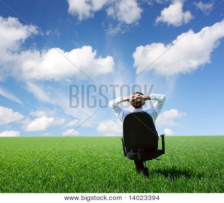 Businessman sitting on chair in green meadow and looking to a blue cloudy sky