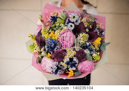 Florist hands with big floral bouquet mix flowers
