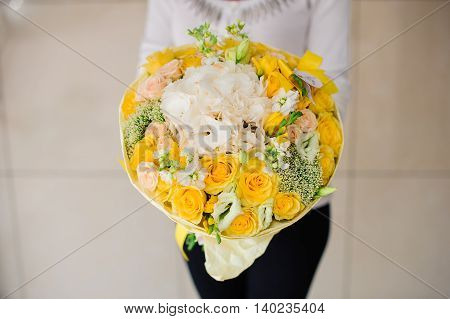 Beautiful bouquet of yellow flowers in hands of the girl no face