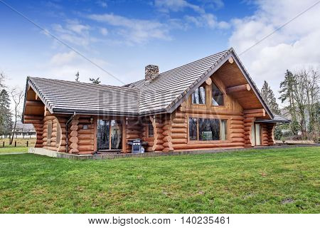 Large Log Cabin House Exterior With Grass Filled Back Yard.