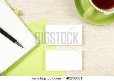 Business card blank, notepad, coffee cup and pen at office desk table top view. Corporate stationery branding mock-up.