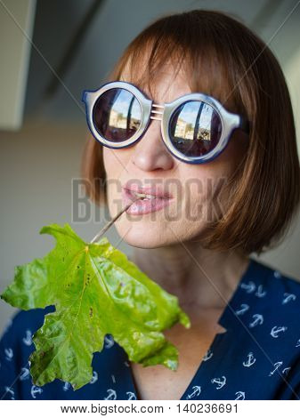 portrait of a woman with glasses and a green leaf the age of forty years