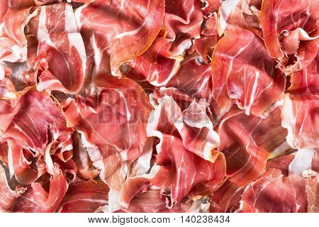 curled slices of delicious Italian Prosciutto on parchment paper on old rustic table blank space left view from above