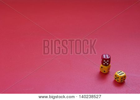 Dices on a matte red background. Concept of luck gambling or chance. Three color dices.