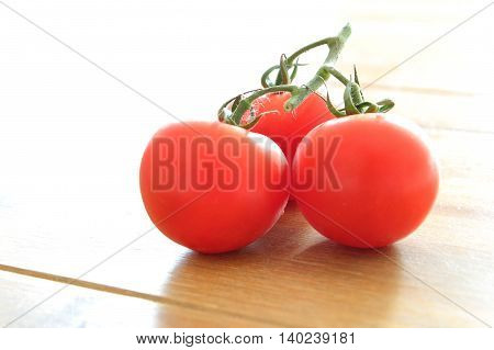 Three Ripe Tomatoes On The Vine With Bright Backlight
