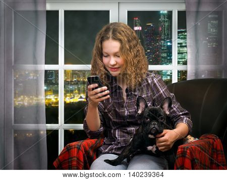 The girl with the phone a smartphone and a dog in his arms on the background of the window. Outside, night city, skyscrapers