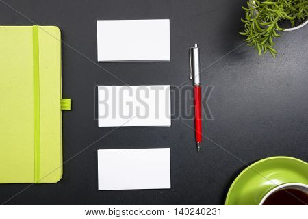 Business card blank, notepad, coffee cup and pen, flower at office desk table top view. Corporate stationery branding mock-up.