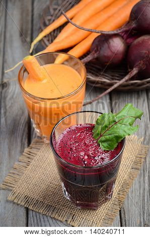 Fresh beetroot and carrot juices on wooden background, selective focus