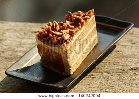 Delicious slice of cake on the plate on the wood foor