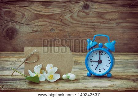 Blue alarm clock empty paper tag jasmine branch old wooden table retro style