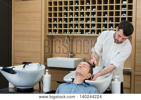 Close-up of a young man having his hair washed in a hairdressing salon.