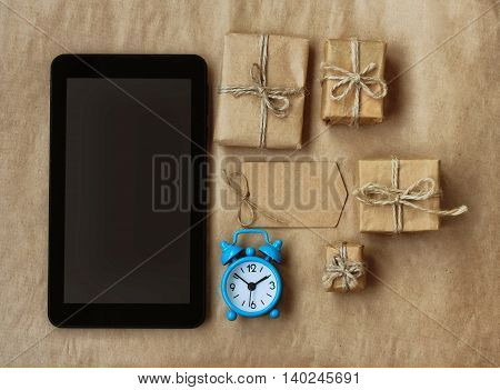 tablet alarm clock gift box in brown wrapping paper envelope tied rope time to shop concept