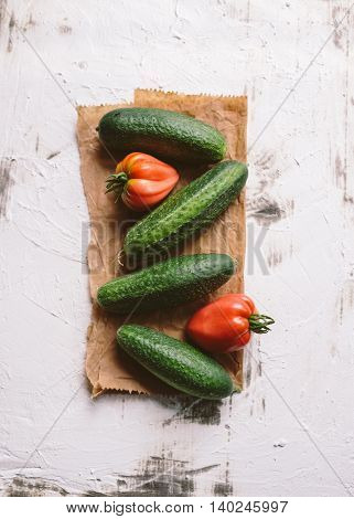 Fresh organic cucumbers and heirloom tomatoes on a piece of paper