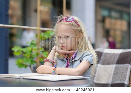 Adorable child reading menu in cafe. Toddler tired girl in beautiful outside cafe choosing meal from menu card. Shop windows in the background. Blond hair fluttering in the wind.