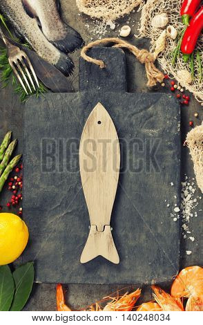 Delicious fresh fish and seafood on vintage background. Fish and shrimps with aromatic herbs, spices and vegetables - healthy food, diet or cooking concept