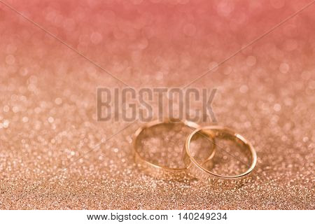 Soft focus of 2 silver rings on glittery background, shallow depth of field with pink filter and copyspace