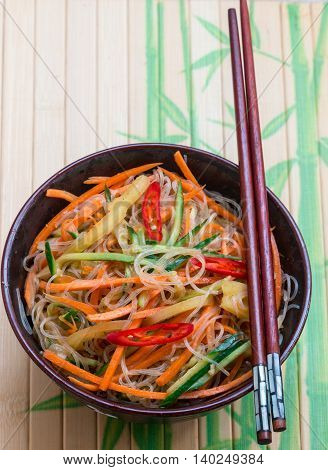 Spicy glass noodles with vegetables - carrots cucumber peppers garlic. Dish Asian and Oriental cuisine. Selective focus