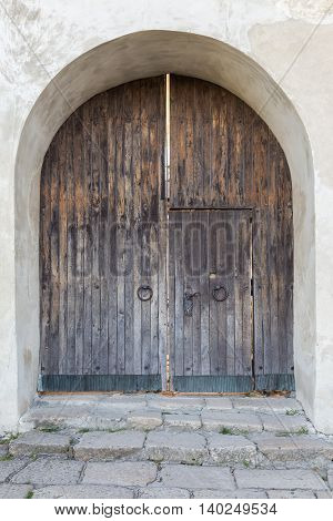 Front view of an ancient wooden gate with door knocker rings