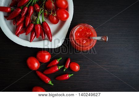 Tomato ketchup sauce with cherry tomatoes and mini red hot chili peppers in a small glass jar with a spoon on dark wooden background. Fresh Homemade Salsa Dip. Top view. Copy space.