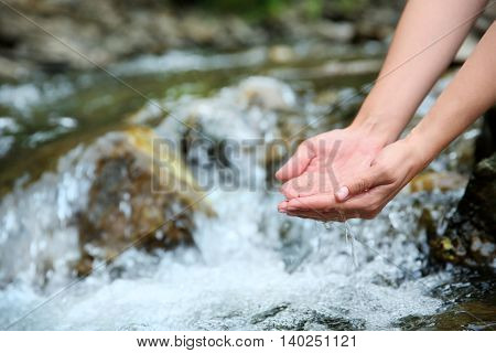 Female hands in water stream