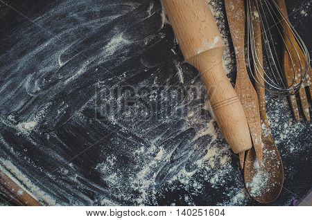 Rural kitchen utensils on blackboard from above - rustic background with free text space. Baking concept. Baking background. Baking preparation. Different stuff. Top view. Copy space.
