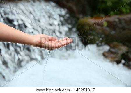Female hand near water stream