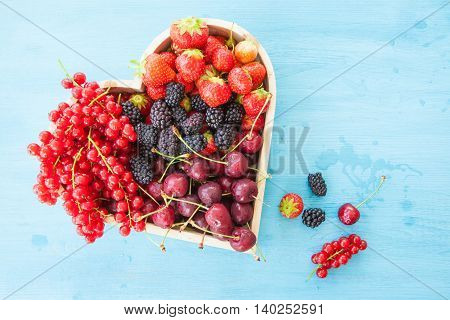 Fresh red berries in a heart-shaped tray on blue wooden background