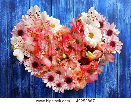 Composition of beautiful flowers in a heart shape on blue wooden background